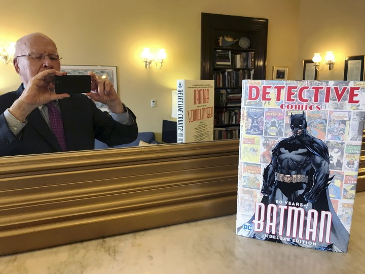 This Thursday, March 28, 2019, photo provided by Sen. Patrick Leahy, D-Vt., shows Leahy in a mirror and the 80th anniversary edition of a book commemorating the superhero Batman. Leahy, who wrote the foreward for the book, has been a Batman fan since first reading the comic books as a child growing up in the 1940s in Montpelier, Vt. Leahy also has made brief appearances in a number of Batman movies. (Sen. Patrick Leahy via AP)