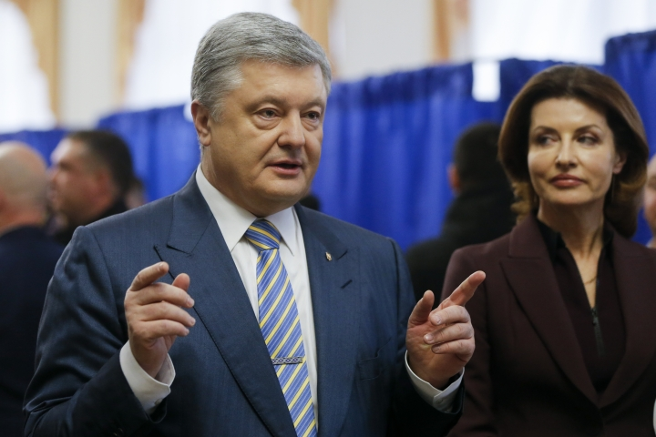 Ukrainian President Petro Poroshenko gestures while speaking to the media, with his wife Maryna, right, at a polling station during the presidential election in Kiev, Ukraine, Sunday, March 31, 2019. Voters in Ukraine are casting ballots in a presidential election Sunday after a campaign that produced a comedian with no political experience as the front-runner and allegations of voter bribery. (AP Photo/Efrem Lukatsky)
