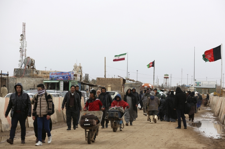 In This Wednesday, Feb. 20, 2019, photo, Afghans return to Afghanistan at the Islam Qala border with Iran, in the western Herat Province. Security officials worry that Iranian-backed Afghan veterans of the war in Syria will one day become a secret army for Tehran in Afghanistan itself, particularly after a U.S. withdrawal. Iran paid, trained and armed thousands of Afghan Shiites to fight in Syria to defend its ally, President Bashar Assad. Returning home as Syria's war winds down, they face suspicion and fear. (AP Photo/Rahmat Gul)