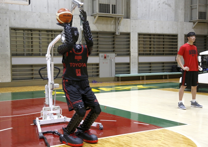 Toyota's basketball robot Cue 3 demonstrates Monday, April 1, 2019 at a gymnasium in Fuchu, Tokyo. The 207-centimeter (six-foot-10) -tall machine made five of eight three-pointer shots in a demonstration in a Tokyo suburb Monday, a ratio its engineers say is worse than usual. Toyota Motor Corp.'s robot, called Cue 3, computes as a three-dimensional image where the basket is, using sensors on its torso, and adjusts motors inside its arm and knees to give the shot the right angle and propulsion for a swish.(AP Photo/Yuri Kageyama)