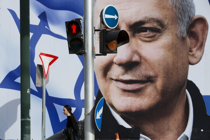 File - In this Thursday, March 28, 2019 file photo, a woman walks by an election campaign billboard showing Israel's Prime Minister Benjamin Netanyahu, the Likud party leader, in Tel Aviv, Israel. An Israeli watchdog said Monday that it's found a network of social media bots disseminating messages in support of Netanyahu ahead of next week's elections. (AP Photo/Oded Balilty, File)