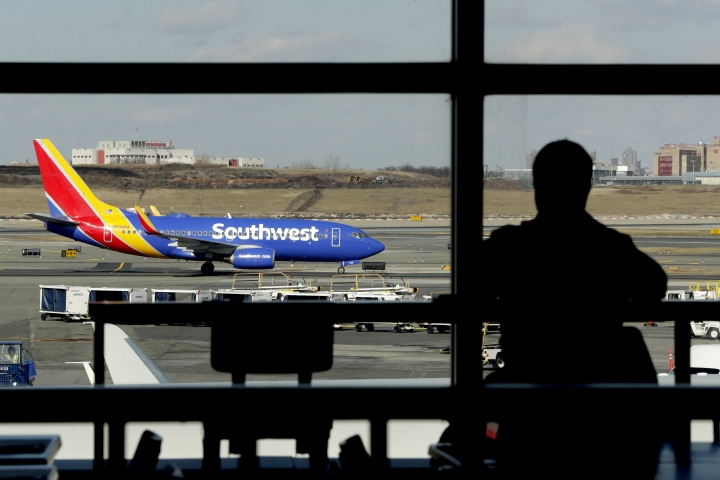 FILE- In this Jan. 25, 2019, file photo a Southwest Airlines jet moves on the runway as a person eats at a terminal restaurant at LaGuardia Airport in New York. A technical outage is impacting major airlines and causing flight delays that may lead to a ripple effect throughout the day. The Federal Aviation Administration said Monday, April 1 that several airlines were dealing with computer issues. Dan Landson of Southwest Airlines said there was an outage with a vendor that services multiple carriers with data used in flight planning. There are delays already at airports in Chicago, New York, Boston, Atlanta, Miami and Detroit. The airline anticipates scattered delays. (AP Photo/Julio Cortez, File)