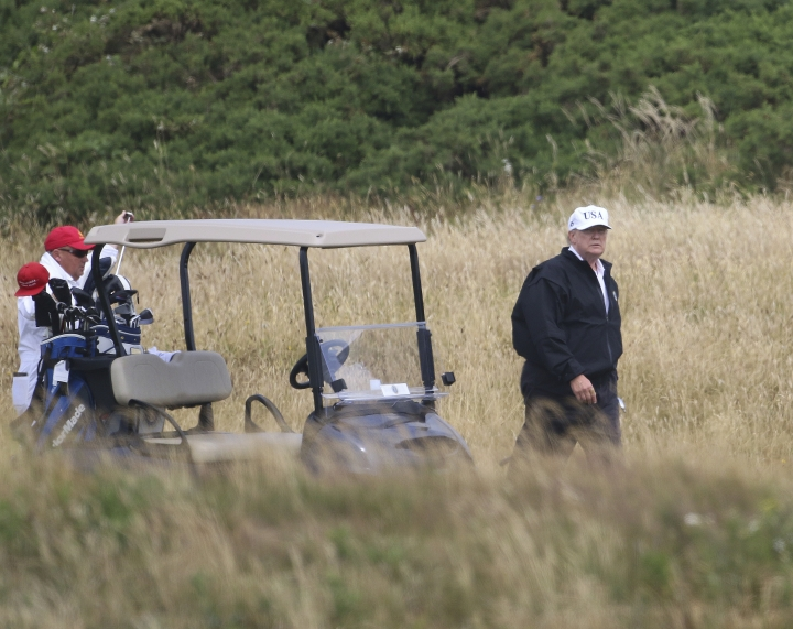 """FILE - In the Saturday, July 14, 2018 file photo, President Donald Trump plays golf at Turnberry golf club, Scotland. Trump's alleged misdeeds on and around the golf course are the subject of a new book by former sports columnist Rick Reilly, called """"Commander in Cheat: How Golf Explains Trump."""" Reilly documents dozens of examples of exaggerations and underhanded play by the president. Reilly tells The Associated Press there have been """"dozens and dozens of people that can declare him guilty of cheating."""" (AP Photo/Peter Morrison)"""