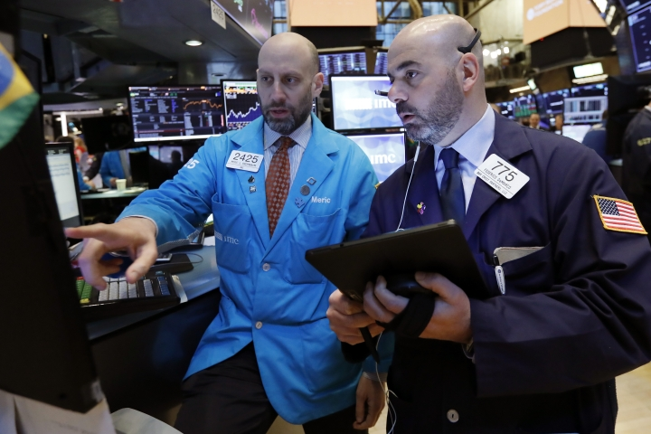 FILE- In this March 18, 2019, file photo specialist Meric Greenbaum, left, and trader Fred DeMarco work on the floor of the New York Stock Exchange. The U.S. stock market opens at 9:30 a.m. EDT on Monday, April 1. (AP Photo/Richard Drew, File)