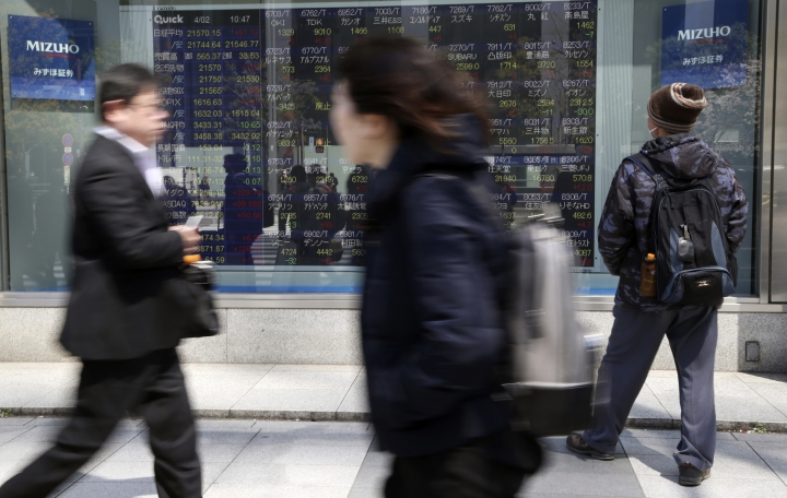People walk by an electronic stock board of a securities firm in Tokyo, Tuesday, April 2, 2019. Asian stock prices followed Wall Street higher on Tuesday on encouraging global economic data. (AP Photo/Koji Sasahara)