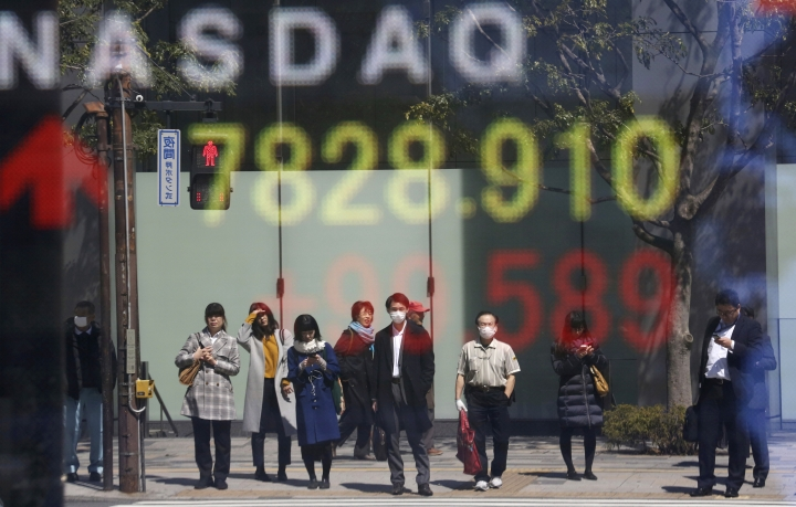 People are reflected on the electronic board of a securities firm in Tokyo, Tuesday, April 2, 2019. Asian stock prices followed Wall Street higher on Tuesday on encouraging global economic data.(AP Photo/Koji Sasahara)