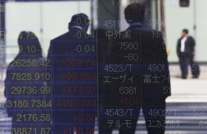 People are reflected on the electronic board of a securities firm in Tokyo, Tuesday, April 2, 2019. Asian stock prices followed Wall Street higher on Tuesday on encouraging global economic data. (AP Photo/Koji Sasahara)