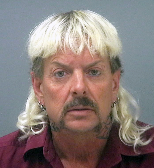 "FILE - This file photo provided by the Santa Rose County Jail in Milton, Fla., shows Joseph Maldonado-Passage. Prosecutors say Maldonado-Passage, also known as ""Joe Exotic, tried to arrange the killing of Carole Baskin, the founder of Big Cat Rescue. Lurors were shown a Facebook video Tuesday, March 26, 2019, that depicts Maldonado-Passage shooting a blow-up ""Carole"" doll in the head. Other videos show him pretending to dig a grave for Baskin and threatening to mail her rattlesnakes. (Santa Rosa County Jail via AP, File)"