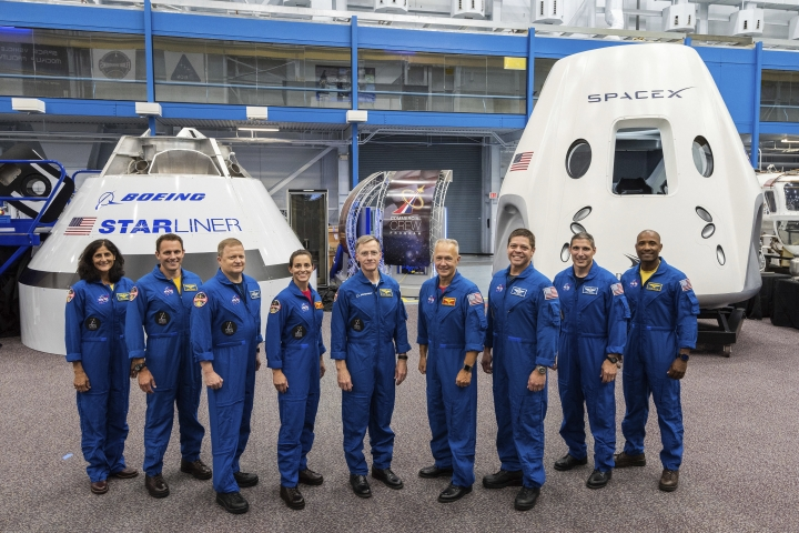 FILE - This undated photo made available by NASA on Aug. 3, 2018 shows mockups of Boeing's CST-100 Starliner and SpaceX's Crew Dragon capsules with crew members, from left, Sunita Williams, Josh Cassada, Eric Boe, Nicole Mann, Christopher Ferguson, Douglas Hurley, Robert Behnken, Michael Hopkins and Victor Glover at the Johnson Space Center in Texas. Boe, pulled for unspecified medical reasons in January 2019, was replaced by Mike Fincke. The Starliner capsule, supposed to make its debut in April 2019, was pushed back until August. SpaceX's Dragon capsule could fly with a test crew in the summer of 2019, but the schedule is under review. (NASA via AP)