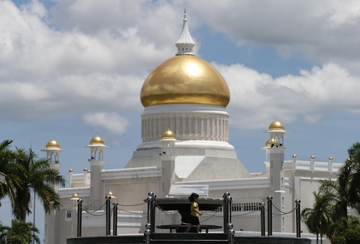 In this April 23, 2013, photo, a child walks near Sultan Omar Ali Saifuddien Mosque, one of the landmarks of Bandar Seri Begawan in Brunei. Brunei announced to implement Islamic criminal laws that punishes gay sex by stoning offenders to death. The legal change in the tiny, oil-rich monarchy, which also includes amputation for theft, is due to come into force Wednesday, April 3, 2019. (AP Photo/Vincent Thian)