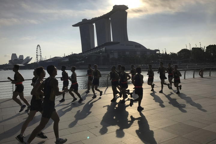 FILE - In this Aug. 4, 2017, file photo, runners are seen in silhouette and their shadows cast on the Marina Bay promenade as they jog at the start of a work day in Singapore. The Marina Bay Sands hotel towers, right, ArtScience Museum, left, and Singapore Flyer, second left, are seen in the background. On Wednesday, April 3, 2019, casino company Las Vegas Sands announced it'll spend $3.3 billion to expand its property in Singapore by adding an entertainment arena, another hotel tower and additional convention space. (AP Photo/Wong Maye-E, File)