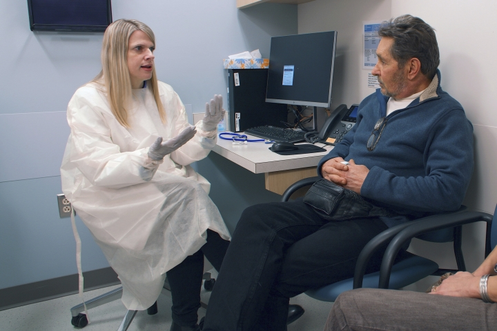 In this February 2019 photo provided by Brigham and Women's Hospital, Dr. Ann Woolley, an infectious disease specialist, speaks with patient Mark Natichinoi at the hospital in Boston. Natichinoi, who received a hepatitis C-positive lung transplant, was given antiviral medicine shortly after the procedure in hopes of blocking hepatitis C infection rather than having to treat it. (Adam Knee/Brigham and Women's Hospital via AP)
