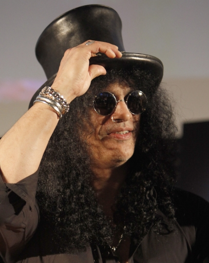 FILE - In this April 22, 2010 file photo, former Guns N' Roses guitarist Slash greets fans during an event in Tokyo, Japan. The former wife of Guns N' Roses guitarist Slash is selling off exotic and erotic items from their 14 years of marriage. Julien's Auctions on Thursday, April 3, 2019 announced the collection from Slash and Perla Hudson's Beverly Hills estate will be part of next month's Music Icons auction. (AP Photo/Shizuo Kambayashi, File)