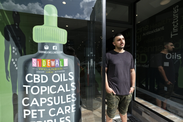 In this photo taken Thursday, March 21, 2019, Gus Dabais stands outside his Sidewalk Wellness store in San Francisco. CBD oil-infused food, drinks and dietary supplements are popular even though the U.S. government says they're illegal and some local authorities have forced retailers to pull products. The confusion has California, Texas and other states moving to legalize the cannabis compound that many see as beneficial to their health. (AP Photo/Eric Risberg)