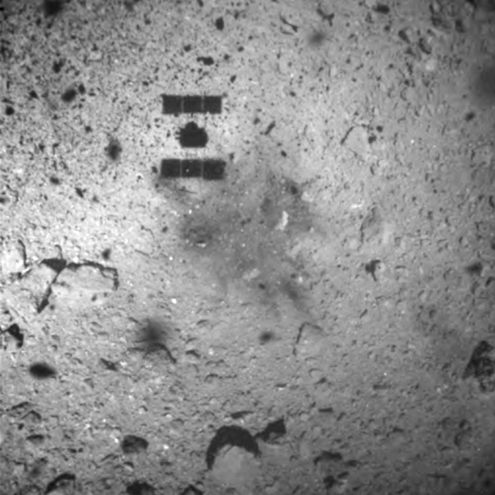 FILE - This Feb. 22, 2019, file image released by the Japan Aerospace Exploration Agency (JAXA) shows the shadow, center above, of the Hayabusa2 spacecraft after its successful touchdown on the asteroid Ryugu. Japan's space agency JAXA said Friday, April 5, 2019, its Hayabusa2 spacecraft released an explosive onto an asteroid to make a crater on its surface and collect underground samples to find possible clues to the origin of the solar system. The mission is the riskiest for Hayabusa2, as it has to immediately get away so it won't get hit by flying shards from the blast. (JAXA via AP, File)