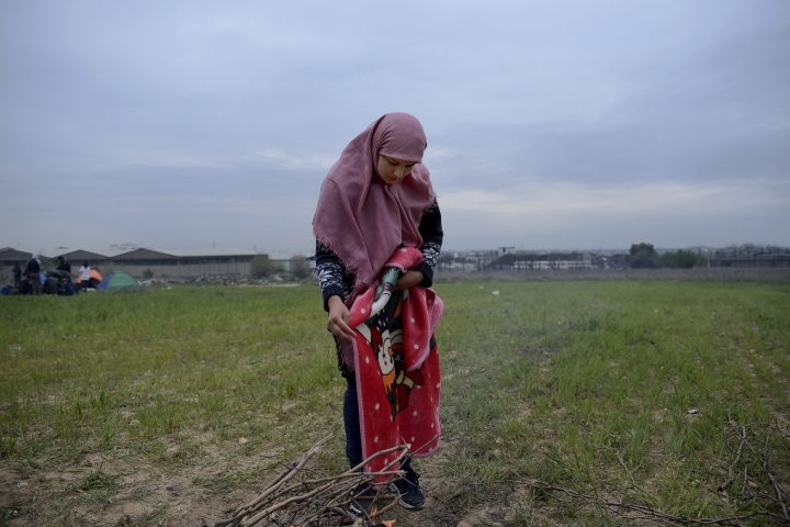 A migrant woman stands at a field outside a refugee camp in the village of Diavata, west of Thessaloniki, northern Greece, Friday, April 5, 2019. Clashes broke out Thursday between migrants and Greek police outside a camp in northern Greece, where hundreds gathered in the hope of reviving a route that saw hundreds of thousands enter more prosperous countries in Europe. (AP Photo/Giannis Papanikos)