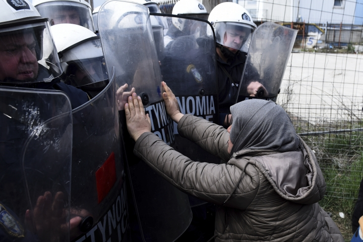A migrant woman pushing with riot police outside a refugee camp in the village of Diavata, west of Thessaloniki, northern Greece, Friday, April 5, 2019. Clashes broke out Thursday between migrants and Greek police outside a camp in northern Greece, where hundreds gathered in the hope of reviving a route that saw hundreds of thousands enter more prosperous countries in Europe. (AP Photo/Giannis Papanikos)