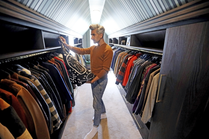"In this March 15, 2019, photo, Tan France, a cast member on the Netflix series ""Queer Eye,"" looks at his clothes in the attic of his home in Salt Lake City. The series touches on some of the country's deepest divides with persistent optimism. The makeover program starring five gay men tackles the contrast between urban and rural, white and black, liberal and conservative. (AP Photo/Rick Bowmer)"