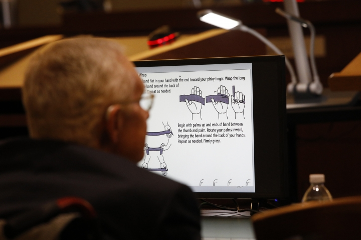 Former U.S. Sen. Harry Reid sits in front of a monitor showing instructions for an exercise band in court Tuesday, March 26, 2019, in Las Vegas. A jury in Nevada heard opening arguments Tuesday in Reid's lawsuit against the maker of a flexible exercise band that he says slipped from his hand while he used it in January 2015, causing him to fall and suffer lasting injuries including blindness in one eye. (AP Photo/John Locher)
