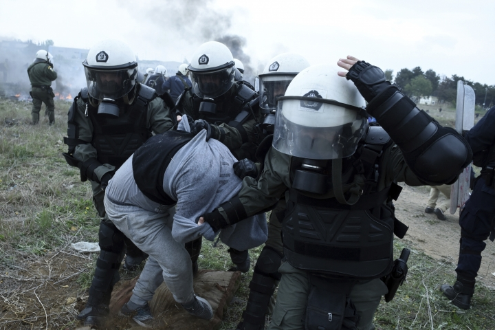 Riot police detain a protesting migrant during clashes outside a refugee camp in the village of Diavata, west of Thessaloniki, northern Greece, Saturday, April 6, 2019. Clashes between hundreds of protesting migrants and police continue for a third day outside an overcrowded migrant camp, with migrants throwing rocks at police and the latter responding with tear gas and stun grenades. (AP Photo/Giannis Papanikos)