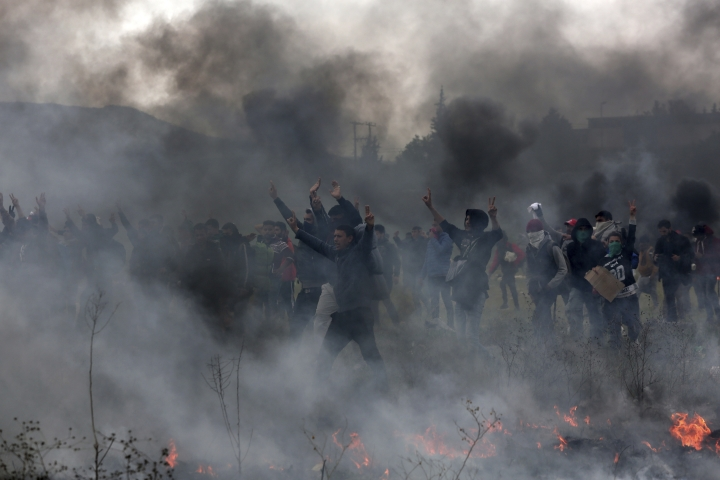 Protesting migrants shout slogans during clashes outside a refugee camp in the village of Diavata, west of Thessaloniki, northern Greece, Saturday, April 6, 2019. Clashes between hundreds of protesting migrants and police continue for a third day outside an overcrowded migrant camp, with migrants throwing rocks at police and the latter responding with tear gas and stun grenades. (AP Photo/Giannis Papanikos)