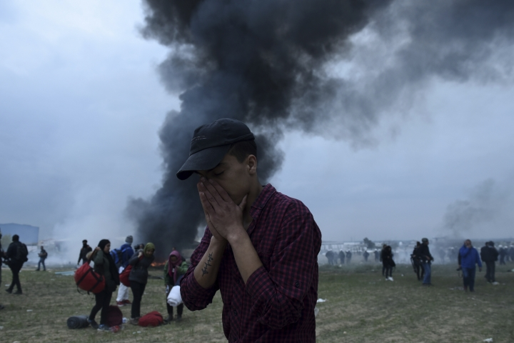 A protesting migrant holds his face during clashes outside a refugee camp in the village of Diavata, west of Thessaloniki, northern Greece, Saturday, April 6, 2019. Clashes between hundreds of protesting migrants and police continue for a third day outside an overcrowded migrant camp, with migrants throwing rocks at police and the latter responding with tear gas and stun grenades. (AP Photo/Giannis Papanikos)