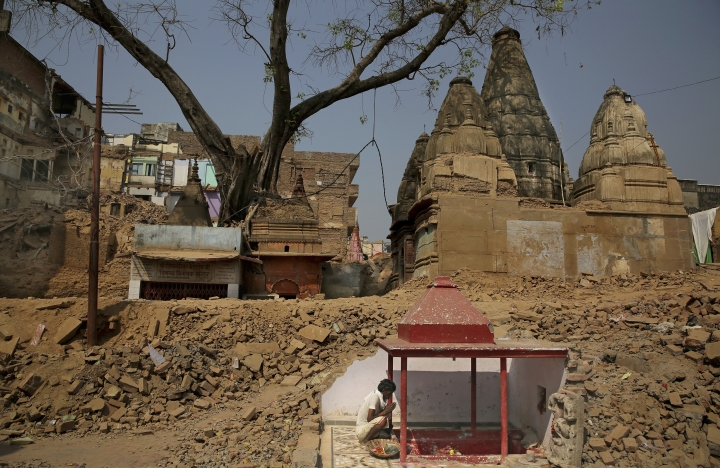 In this March 19, 2019 photo, a Hindu man prays next to a small temple uncovered hidden within the wall of demolished buildings at the site of a proposed grand promenade connecting the sacred Ganges river with a centuries-old temple dedicated to Lord Shiva, in Varanasi, India. The demolition of around 300 commercial and residential buildings between the temple and the river have left a gaping hole in Varanasi's urban core, a congested maze of zig-zagging brick lanes full of religious shrines. (AP Photo/Altaf Qadri)