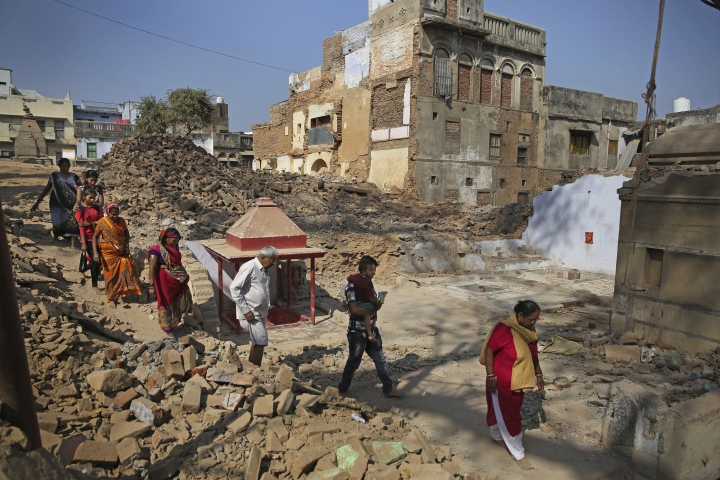 In this March 19, 2019 photo, Hindu devotees walk barefoot through debris of demolished houses to reach river Ganges at the site of a proposed grand promenade connecting the sacred Ganges river with a centuries-old temple dedicated to Lord Shiva, in Varanasi, India. The $115 million promenade is just one of a number of India Prime Minister Narendra Modi's religious glamor projects, aimed squarely at pleasing his Hindu nationalist base ahead of elections that start this month. (AP Photo/Altaf Qadri)