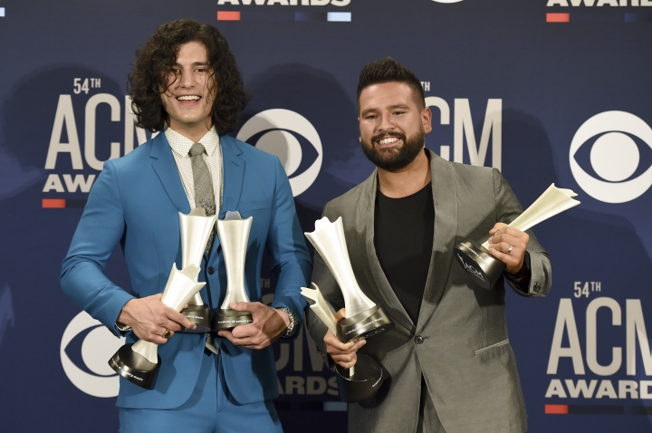 "Dan Smyers, left, and Shay Mooney, of Dan + Shay, pose in the press room with the awards for song of the year and single of the year for ""Tequila,"" and duo of the year at the 54th annual Academy of Country Music Awards at the MGM Grand Garden Arena on Sunday, April 7, 2019, in Las Vegas. (Photo by Jordan Strauss/Invision/AP)"