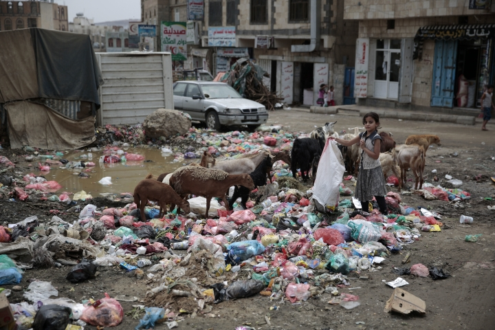 FILE - In this July 26, 2017 file photo, a girl scavenges for recyclable items at a garbage dump in a street in Sanaa, Yemen. An Associated Press investigation finds that Yemen's massive cholera epidemic was aggravated by corruption and official intransigence. The investigation has found that both the Iranian-backed Houthis rebels and their main adversary in the war -- the U.S.- and Saudi-backed government that controls southern Yemen -- impeded efforts by relief groups to stem the epidemic. (AP Photo/Hani Mohammed, File)