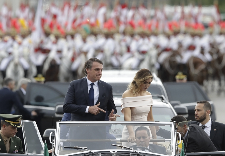 FILE - In this Jan. 1, 2019 file photo, Brazil's President Jair Bolsonaro points with his fingers to mimic guns as he rides in an open car with his wife, first lady Michelle Bolsonaro, after his swearing-in ceremony in Brasilia, Brazil. In his first 100 days in office, the anti-corruption and pro-gun outsider has scored only a few major victories to keep his far-right base excited. (AP Photo/Andre Penner, File)