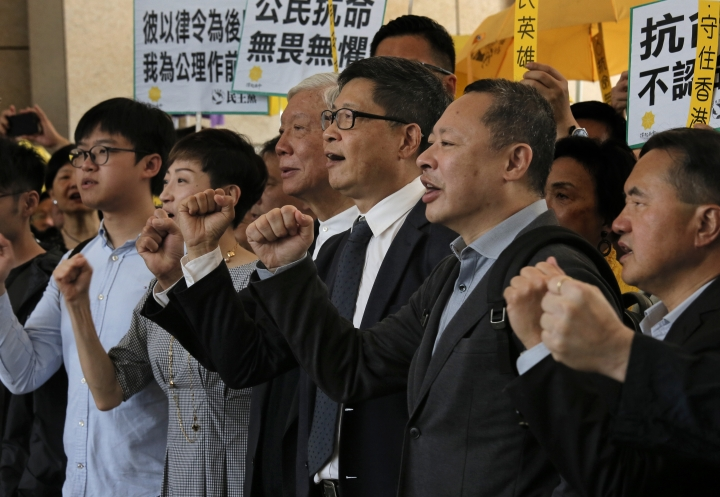 "Occupy Central leaders, from right, Benny Tai, Chan Kin-man, Chu Yiu-ming, Tanya Chan and Eason Chung shout slogans before entering a court in Hong Kong, Tuesday, April 9, 2019. Nine leaders of the 2014 Hong Kong pro-democracy movement arrived the court to hear the verdicts in their trial. The co-founders of the ""Occupy Central"" campaign - legal Professor Benny Tai, sociology professor Chan Kin-man and retired pastor Chu Yiu-ming - are facing charges related to the planning and implementation of the campaign which became part of the large-scale pro-democracy Umbrella Movement protests which were carried out 79 days between September and December 2014. (AP Photo/Vincent Yu)"