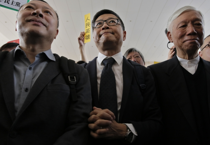 "Occupy Central leaders, from left, Benny Tai, Chan Kin-man and Chu Yiu-ming shout slogans before entering a court in Hong Kong, Tuesday, April 9, 2019. Nine leaders of the 2014 Hong Kong pro-democracy movement are scheduled to hear the verdicts in their trial. The co-founders of the ""Occupy Central"" campaign - legal Professor Benny Tai, sociology professor Chan Kin-man and retired pastor Chu Yiu-ming - are facing charges related to the planning and implementation of the campaign which became part of the large-scale pro-democracy Umbrella Movement protests which were carried out 79 days between September and December 2014. (AP Photo/Vincent Yu)"