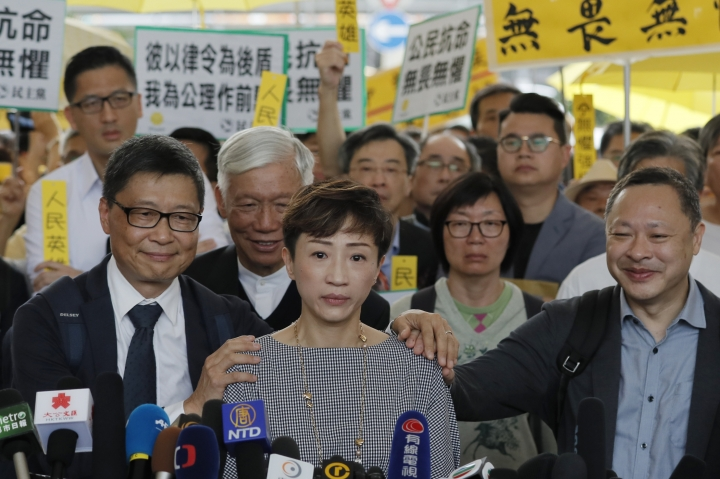 """Occupy Central leaders, Tanya Chan, center, speaks next to Benny Tai, right, Chan Kin-man, left, and Chu Yiu-ming, second left, before entering a court in Hong Kong, Tuesday, April 9, 2019. Nine leaders of the 2014 Hong Kong pro-democracy movement hear the verdicts in their trial. The co-founders of the """"Occupy Central"""" campaign - legal Professor Benny Tai, sociology professor Chan Kin-man and retired pastor Chu Yiu-ming - are facing charges related to the planning and implementation of the campaign which became part of the large-scale pro-democracy Umbrella Movement protests which were carried out 79 days between September and December 2014. (AP Photo/Kin Cheung)"""