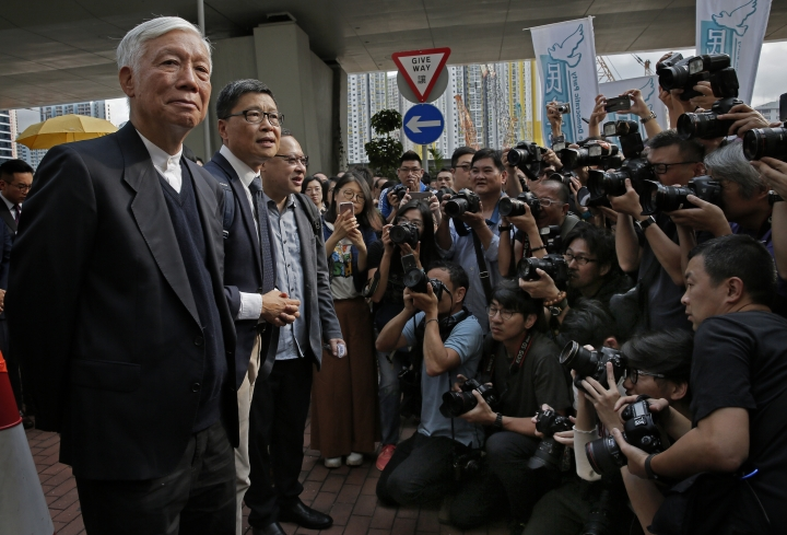 """Occupy Central leaders, from left, Chan Kin-man, Chu Yiu-ming and Benny Tai pose for photographers before entering a court in Hong Kong, Tuesday, April 9, 2019. Nine leaders of the 2014 Hong Kong pro-democracy movement are scheduled to hear the verdicts in their trial. The co-founders of the """"Occupy Central"""" campaign - legal Professor Benny Tai, sociology professor Chan Kin-man and retired pastor Chu Yiu-ming - are facing charges related to the planning and implementation of the campaign which became part of the large-scale pro-democracy Umbrella Movement protests which were carried out 79 days between September and December 2014. (AP Photo/Vincent Yu)"""