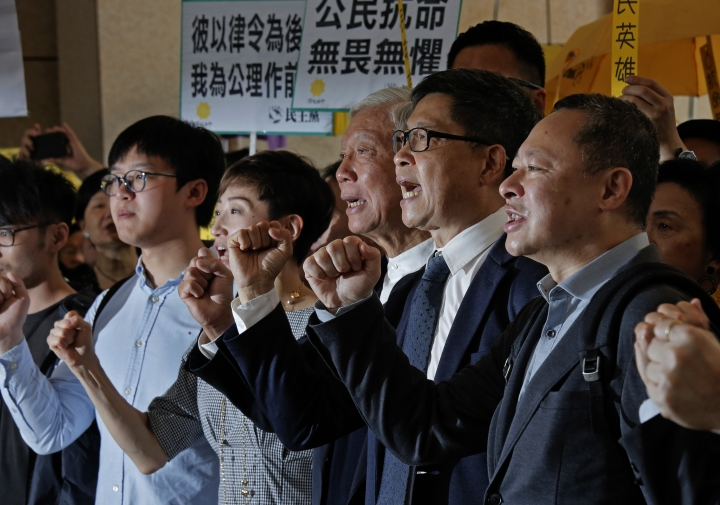 """Occupy Central leaders, from right, Benny Tai, Chan Kin-mMan, Chu Yiu-ming, Tanya Chan and Eason Chung shout slogans before entering a court in Hong Kong, Tuesday, April 9, 2019. Nine leaders of the 2014 Hong Kong pro-democracy movement arrived the court to hear the verdicts in their trial. The co-founders of the """"Occupy Central"""" campaign - legal Professor Benny Tai, sociology professor Chan Kin-man and retired pastor Chu Yiu-ming - are facing charges related to the planning and implementation of the campaign which became part of the large-scale pro-democracy Umbrella Movement protests which were carried out 79 days between September and December 2014. (AP Photo/Vincent Yu)"""