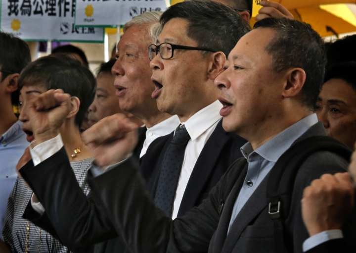 """Occupy Central leaders, from right, Benny Tai, Chan Kin-man and Chu Yiu-ming shout slogans before entering a court in Hong Kong, Tuesday, April 9, 2019. Nine leaders of the 2014 Hong Kong pro-democracy movement are scheduled to hear the verdicts in their trial. The co-founders of the """"Occupy Central"""" campaign - legal Professor Benny Tai, sociology professor Chan Kin-man and retired pastor Chu Yiu-ming - are facing charges related to the planning and implementation of the campaign which became part of the large-scale pro-democracy Umbrella Movement protests which were carried out 79 days between September and December 2014. (AP Photo/Vincent Yu)"""