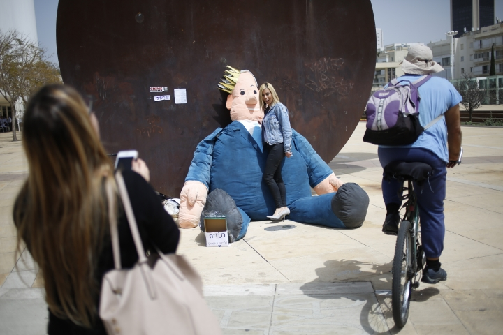 A woman poses by a doll made to resemble Israel's Prime Minister Benjamin Netanyahu in Tel Aviv, Israel, Sunday, April 7, 2019. Israel's election on Tuesday boils down to a referendum on Prime Minister Benjamin Netanyahu, who has dominated the country's politics for the better part of three decades. (AP Photo/Ariel Schalit)