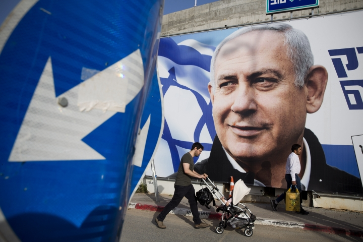 A man walks by an election campaign billboard showing Israel's Prime Minister Benjamin Netanyahu, the Likud party leader, in Tel Aviv, Israel, Sunday, April 7, 2019. Israel's election on Tuesday boils down to a referendum on Prime Minister Benjamin Netanyahu, who has dominated the country's politics for the better part of three decades. (AP Photo/Oded Balilty)