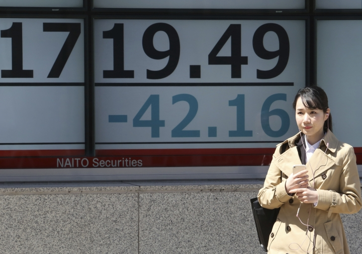 A woman stands by an electronic stock board of a securities firm in Tokyo, Tuesday, April 9, 2019. Asian markets have followed Wall Street higher as investors watched for Brexit developments and corporate earnings. Benchmarks in Shanghai, Hong Kong and Seoul gained, while Tokyo was flat. (AP Photo/Koji Sasahara)