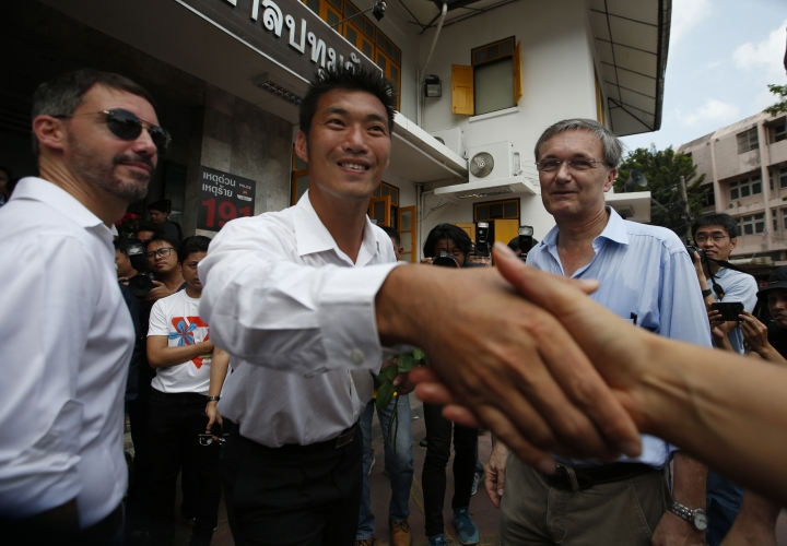 In this Saturday, April 6, 2019, photo, Thailand's Future Forward Party leader Thanathorn Juangroongruangkit shakes hands with his supporters as he stands alongside the First Secretary of the French Embassy in Thailand Christophe Carlucci, left, and Counsellor of the German Embassy in Thailand Alexander Nowak, right, at a police station in Bangkok, Thailand. (AP Photo/Sakchai Lalit)