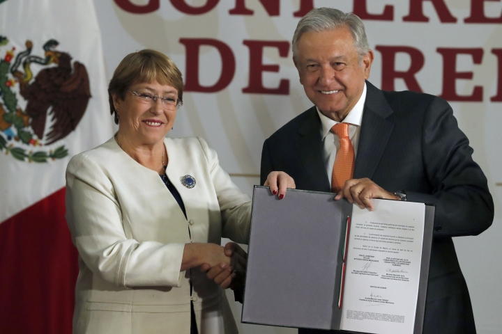 Michelle Bachelet, United Nations High Commissioner for Human Rights and Mexican President Andres Manuel Lopez Obrador, pose for photos after signing their agreement during a ceremony at the National Palace in Mexico City, Tuesday, April 9, 2019. Bachelet said Tuesday that her office will offer technical assistance to ensure that Mexico's newly formed National Guard respects human rights. (AP Photo/Marco Ugarte)