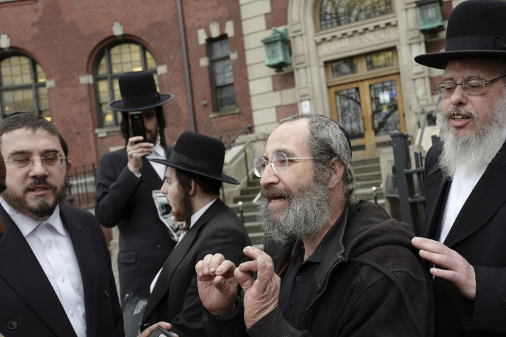A man, center, who would not identify himself, talks to the media about the measles outbreak, Tuesday, April 9, 2019, in the Williamsburg section of New York. He said the he has had his children vaccinated but he respects the right of other parents to decide not to have their children vaccinated. The city health department ordered all ultra-Orthodox Jewish schools in a neighborhood of Brooklyn on Monday to exclude unvaccinated students from classes during the current measles outbreak. In issuing the order, the health department said that any yeshiva in Williamsburg that does not comply will face fines and possible closure.(AP Photo/Mark Lennihan)