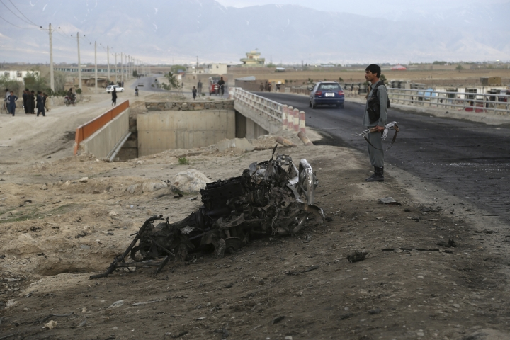 An Afghan security force stand guard at the site a day after an a suicide attack near the Bagram Air Base, north of Kabul, Afghanistan, Tuesday, April 9, 2019. Three American service members and a U.S. contractor were killed when their convoy hit a roadside bomb on Monday near the main U.S. base in Afghanistan, the U.S. forces said. The Taliban claimed responsibility for the attack. (AP Photo/Rahmat Gul)