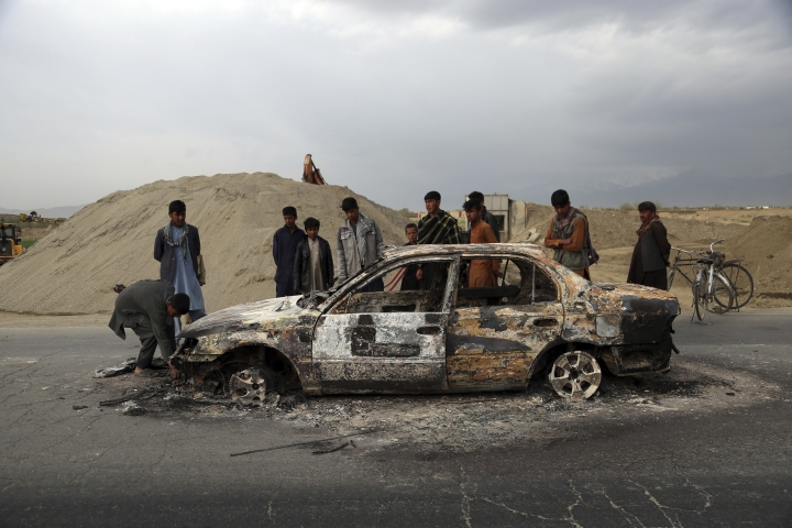 Afghans watch a civilian vehicle burnt after being shot by US forces following an attack near the Bagram Air Base, north of Kabul, Afghanistan, Tuesday, April 9, 2019. Three American service members and a U.S. contractor were killed when their convoy hit a roadside bomb on Monday near the main U.S. base in Afghanistan, the U.S. forces said. The Taliban claimed responsibility for the attack. (AP Photo/Rahmat Gul)