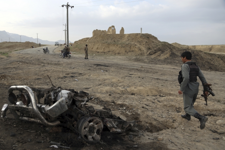 Afghan security forces gather at the site of Monday's attack near the Bagram Air Base, north of Kabul, Afghanistan, Tuesday, April 9, 2019. Three American service members and a U.S. contractor were killed when their convoy hit a roadside bomb on Monday near the main U.S. base in Afghanistan, the U.S. forces said. The Taliban claimed responsibility for the attack. (AP Photo/Rahmat Gul)
