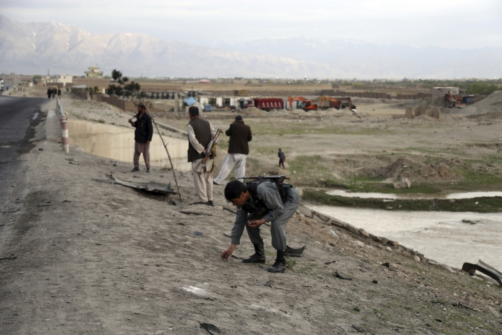 An Afghan security force collect bullet shell a day after an attack near the Bagram Air Base, north of Kabul, Afghanistan, Tuesday, April 9, 2019. Three American service members and a U.S. contractor were killed when their convoy hit a roadside bomb on Monday near the main U.S. base in Afghanistan, the U.S. forces said. The Taliban claimed responsibility for the attack. (AP Photo/Rahmat Gul)