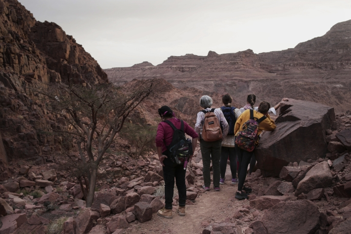 In this March 29, 2019 photo, tourists stop to look at the scenery on a trek in the mountains near Wadi Sahw led by Beduin women, Abu Zenima, in South Sinai, Egypt. Four Bedouin women are for the first time leading tours in Egypt's Sinai Peninsula, breaking new ground in their deeply conservative community, where women almost never work outside the home or interact with outsiders. (AP Photo/Nariman El-Mofty)