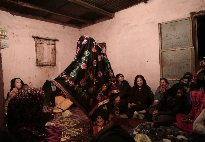 In this March 30, 2019 photo, a Bedouin woman wears traditional clothes and dances for women tourists in Umm Yasser's home, in Wadi Sahw, Abu Zenima, in South Sinai, Egypt. Four Bedouin women are for the first time leading tours in Egypt's Sinai Peninsula, breaking new ground in their deeply conservative community, where women almost never work outside the home or interact with outsiders. The women guide groups of female tourists through the stunning mountain landscapes, part of a Bedouin-led project of hiking tours in southern Sinai. (AP Photo/Nariman El-Mofty)