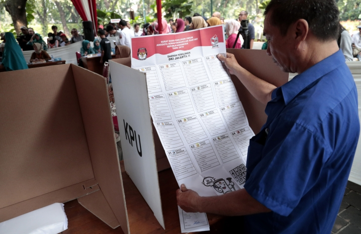 A man inspects a mock national legislature ballot in a voting booth during a polling simulation exercise held by the election commission in Jakarta, Indonesia, Wednesday, April 10, 2019. When Indonesians vote in presidential and legislative elections next week, they'll be wrestling with choices affecting their country's future, and ballots as big as giant posters. (AP Photo/Dita Alangkara)